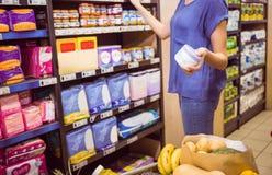 Femme occasionnelle prenant le produit sur l'étagère Images stock
