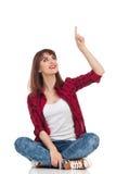 Femme occasionnelle s'asseyante se dirigeant au-dessus de la tête Photos stock