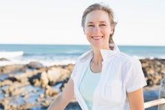 Femme occasionnelle souriant à l'appareil-photo par la mer Image stock