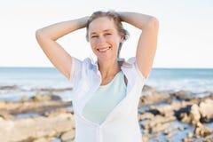 Femme occasionnelle souriant à l'appareil-photo par la mer Photos libres de droits