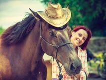 Femme occidentale étreignant le chapeau de cowboy de port de cheval images libres de droits