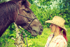Femme occidentale prenant soin de cheval sur le pré Photographie stock libre de droits