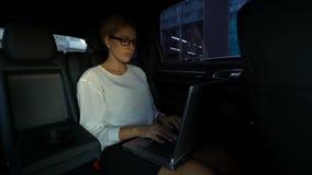 Femme occupée dactylographiant son discours sur l'ordinateur portable, conduisant à la réunion d'affaires dans le taxi banque de vidéos