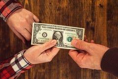 Femme offrant un billet d'un dollar pour équiper Photographie stock libre de droits