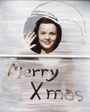 Femme ondulant à la fenêtre avec la salutation de Noël (toutes les personnes représentées ne sont pas plus long vivantes et aucun photo stock