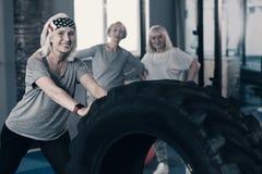 Femme optimiste établissant avec le pneu dans le gymnase Photo libre de droits