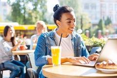 Femme optimiste causant tout en attendant des amis en café Image stock