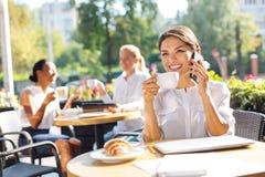 Femme optimiste riant tout en parlant au téléphone en café Photos stock
