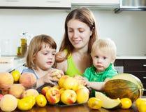 Femme ordinaire avec des filles mangeant des fruits Image libre de droits