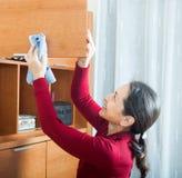 Femme ordinaire nettoyant les meubles en bois images libres de droits