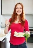 Femme ordinaire positive mangeant la pomme de terre photographie stock
