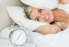Femme oreilles d'une bâche avec l'oreiller comme elle regarde le réveil Photos libres de droits