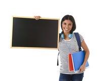 Femme ou étudiante hispanique tenant le tableau noir vide avec l'espace de copie pour ajouter le message Images stock