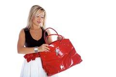 Femme ouvrant le sac rouge d'isolement sur le blanc images libres de droits