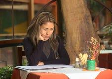 Femme péruvien regardant la carte dans un restaurant Images stock