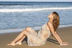 Femme paisible dans la robe d'été reposant Sandy Beach Images libres de droits