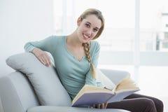 Femme paisible satisfaite détendant lisant un livre se reposant sur le divan photos stock