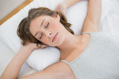 Femme paisiblement de sommeil se trouvant sur son lit blanc images stock