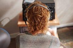 Femme par derrière les écouteurs de port écoutant la musique Photo libre de droits