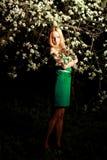 Femme par des fleurs sur l'arbre dans la nuit, poses photos stock