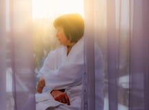 Femme par la lumière du soleil de fenêtre Photo stock