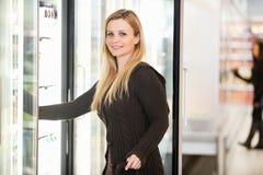 Femme par le refroidisseur d'épicerie Photographie stock libre de droits