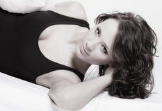 Femme paresseuse de fille sexy avec l'oreiller sur le lit dans la chambre à coucher Photographie stock libre de droits