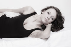 Femme paresseuse de fille sexy avec l'oreiller sur le lit dans la chambre à coucher Images stock