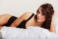 Femme paresseuse de fille sexy dans les sous-vêtements se trouvant sur le lit Image stock