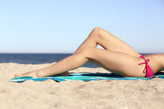 Femme parfaite de beauté cirant des jambes prenant un bain de soleil sur la plage Photos stock