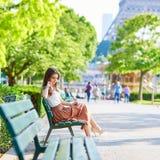Femme parisienne s'asseyant sur le banc près de Tour Eiffel Photographie stock