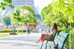 Femme parisienne s'asseyant sur le banc près de Tour Eiffel Image stock