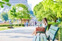Femme parisienne s'asseyant sur le banc près de Tour Eiffel Images stock