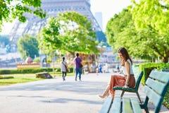 Femme parisienne s'asseyant sur le banc près de Tour Eiffel Images libres de droits