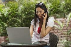 Femme parlant à un téléphone portable et à l'aide d'un ordinateur portable Photos libres de droits