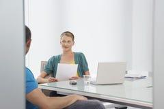 Femme parlant au collègue cultivé dans le bureau Photos stock