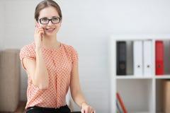 Femme parlant au téléphone au travail dans le bureau Image libre de droits