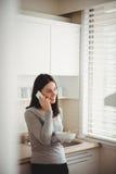Femme parlant au téléphone intelligent tout en tenant le bol de nourriture Image libre de droits