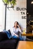 Femme parlant au téléphone portable avec l'ami tout en seul se reposant dans le café moderne Images stock