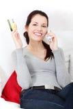 Femme parlant au téléphone, retenant un par la carte de crédit. Photo stock