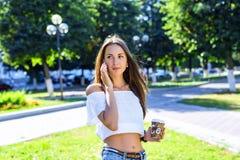 Femme parlant au téléphone, tenant un café ou un thé, belle fille de brune, se tenant en parc, été, chemisier blanc Photo stock