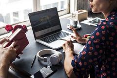 Femme parlant avec le collègue et à l'aide de l'ordinateur portable Image libre de droits