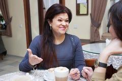 Femme parlant dans un petit rétro café Images stock