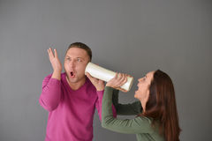 Femme parlant par le tube et une position d'homme Photos stock