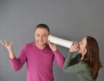 Femme parlant par le tube et une position d'homme Photographie stock libre de droits