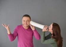 Femme parlant par le tube et une position d'homme Image stock