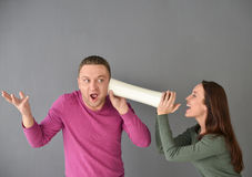 Femme parlant par le tube et une position d'homme Images stock