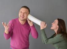 Femme parlant par le tube et une position d'homme Photo libre de droits
