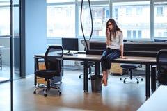 Femme parlant seul au téléphone dans le bureau photos stock