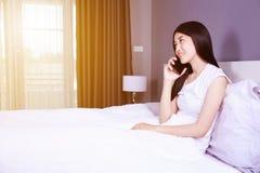 Femme parlant sur le téléphone portable sur le lit dans la chambre à coucher Photographie stock libre de droits